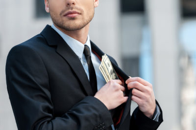 Pocketing company money. Cropped shot of a businessman placing m